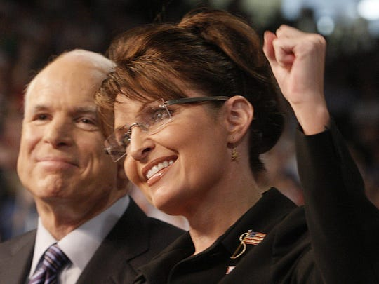 Presumptive Republican presidential nominee Sen. John McCain smiles as his vice presidential running mate, Alaska Gov. Sarah Palin, pumps her fist as she is introduced to supporters at a campaign rally in Dayton, Ohio, on Aug. 29, 2008.
