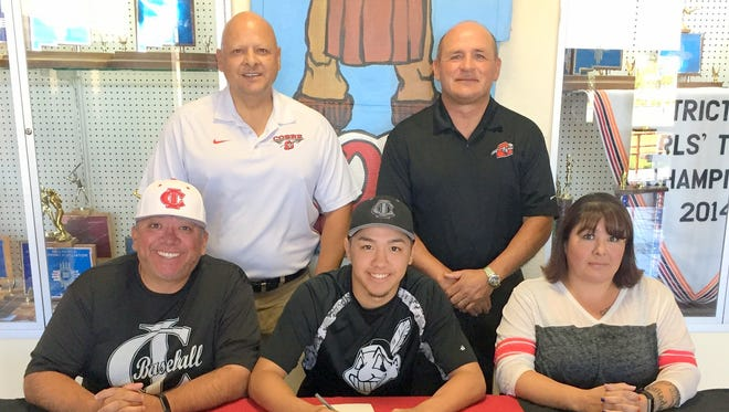 Andru Sanchez, middle, signs his letter of intent to play baseball for Luna Community College. His father and Cobre High head baseball coach Artie Sanchez, left, and mother Amanda Sanchez, right look on. Standing from left, are Cobre athletic director Pat Abalos and Cobre principal Frank Quarrell.