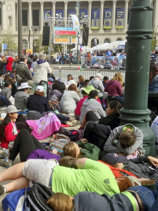 People rest in or near the streets as they await Pope Francis' Mass yesterday in Philadelphia.