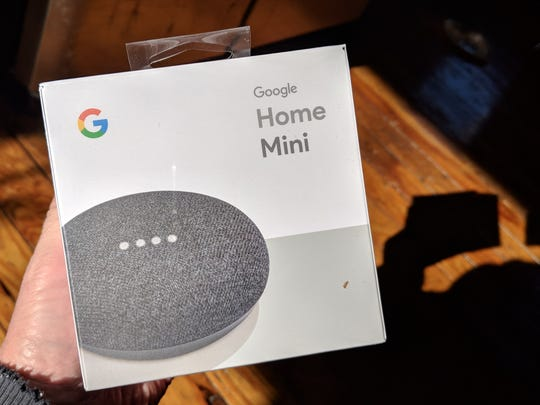 A Google Home Mini as it arrives in the one pound box. The device fits in your hand when unpacked.