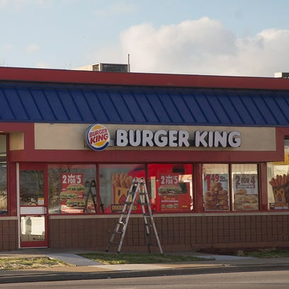 Workers repair a sign on a Burger King restaurant in December 1, 2015.