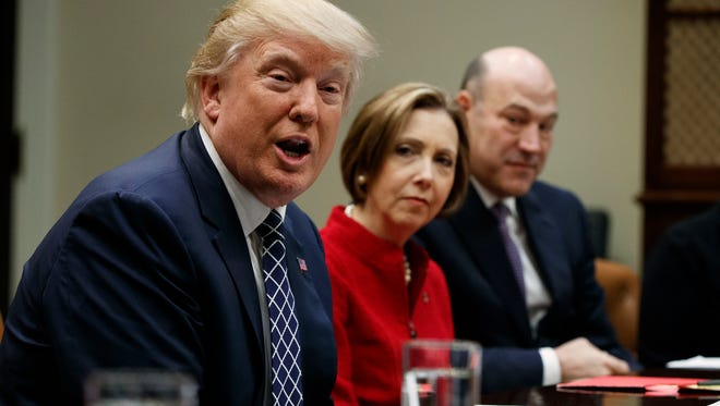 President Donald Trump, accompanied by Cape Cod Five Cents Savings Bank CEO Dorothy Savarese (center) and National Economic Council Director Gary Cohn, speaks during a meeting with leaders from small community banks March 9, 2017, in the Roosevelt Room of the White House in Washington.