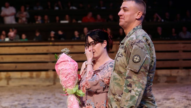 Sgt. Bryan Samsel's wife, Shannon, wipes a tear from her eye in the arena at Dolly Parton's Stampede after being surprised by her husband, who just returned home after a one- year deployment to the Middle East.