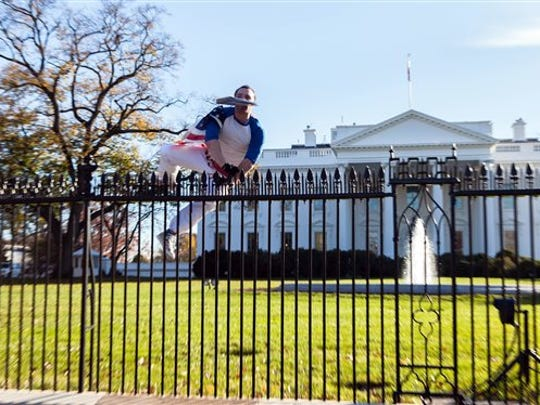In this photo provided by Vanessa Pena, a man jumps a fence at the White House on Thursday, Nov. 26, 2015, in Washington. The man was immediately apprehended and taken into custody pending criminal charges, the Secret Service said. President Barack Obama and his wife and daughters were spending Thanksgiving the holiday at the White House.