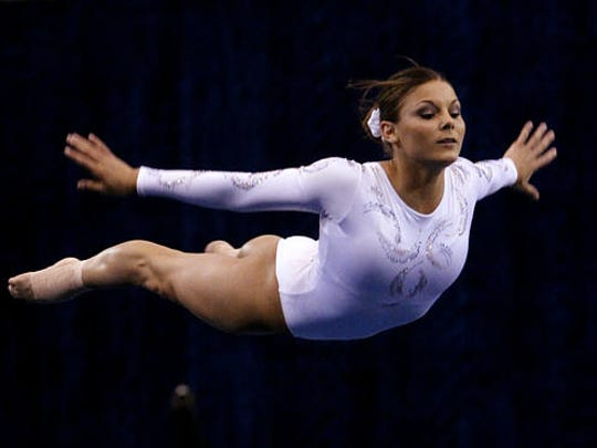 FILE - In this April 15, 2004 file photo Jamie Dantzscher performs her floor routine during preliminaries at the NCAA women's gymnastics championships in Los Angeles. Dantzscher a 2000 Olympian is one of dozens of women and girls, that have filed civil lawsuits against Dr. Larry Nassar a former Michigan State University doctor who specialized in treating elite U.S. gymnasts. Nassar was charged Wednesday, Feb. 22, 2017 with sexually assaulting nine girls, in a court in Ingham County, Mich.