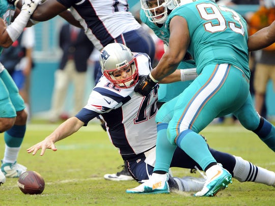Jan 3, 2016; Miami Gardens, FL, USA; New England Patriots quarterback Tom Brady (12) reaches for a ball that he fumbles as Miami Dolphins defensive tackle Ndamukong Suh (93) holds his jersey in the fourth quarter at Sun Life Stadium. Mandatory Credit: Robert Duyos-USA TODAY Sports