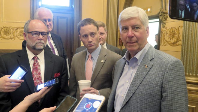 Michigan Gov. Rick Snyder, right, House Speaker Tom Leonard, center, and Senate Majority Leader Arlan Meekhof, left, speak to reporters at the Capitol in Lansing, Mich.