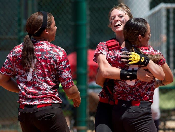 Ali Cutaio (center) of West Florida High School hugs teammate Korina Rosario following the Jaguars' 3-0 win over Gulliver Preparatory in their FHSAA state semifinal game in Vero Beach. Jordaine Wakins stands at left. (Photo by Sam Wolfe)