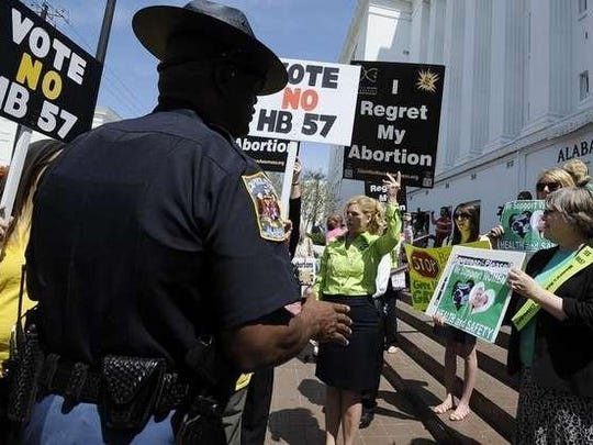 A state trooper speaks with abortion rights and anti-abortion rights activists at the State House in 2013.