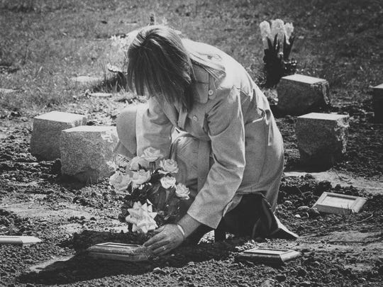 A woman mourning the loss of her pet places flowers at her dog's grave at the Delaware SPCA cemetery in April 1979.