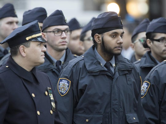 In this Friday, Jan. 13, 2017, photo, Gurpreet Singh, center, who is currently a recruit in the police academy and set to graduate in March 2017, arrives for the funeral service for New York City police officer Steven McDonald, at St. Patrick's Cathedral in New York. Police departments around the country, compelled by a hiring crisis and eager for a more diverse applicant pool, are relaxing traditional grooming standards. That means more officers are on the job with tattoos inked on forearms and biceps, wearing religious headgear like hijabs and turbans, and growing out beards. (AP Photo/Mary Altaffer)