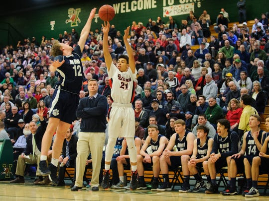 Rutland's Jamison Evans (21) shoots a three pointer over Mount Mansfield's Asa Carlson (12) during the Vermont state division I boys basketball championship game between the Mount Mansfield Cougars and the Rutland Raiders at Patrick Gym on Saturday afternoon March 17, 2018 in Burlington.