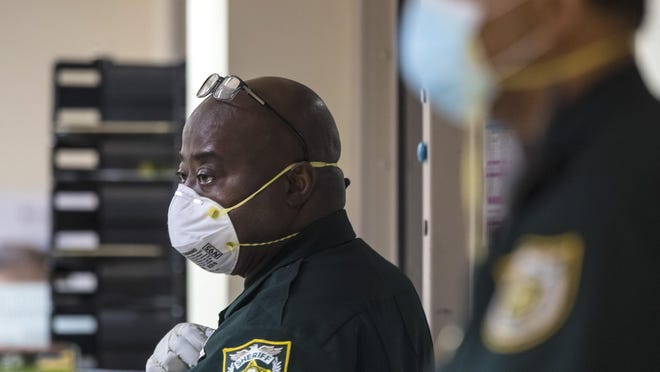 Two PBSO deputies wear masks during hearings in the 1st appearance courtroom Friday, April 24, 2020. The proceedings are now held by video, with inmates either in isolation, or a holding cell outside the courtroom.