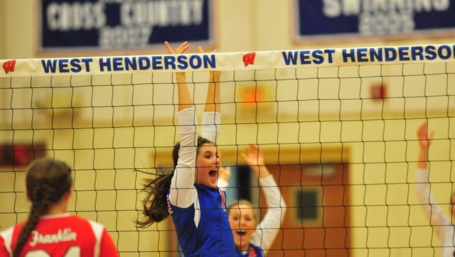 West Henderson volleyball players celebrate a point Tuesday night in their home match with Franklin.