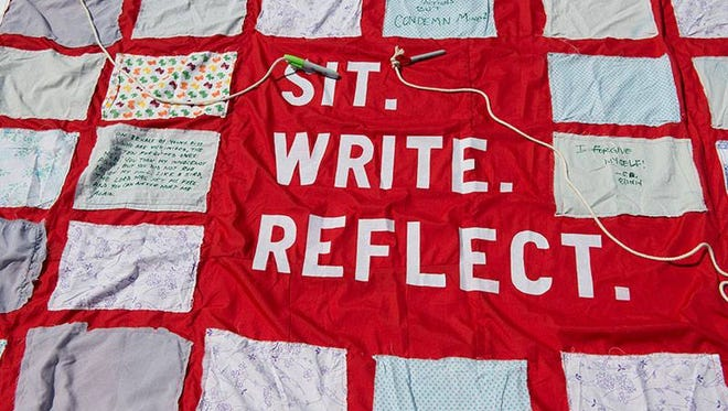 The nationally touring Monument Quilt invites viewers to read stories of abuse and add their own.