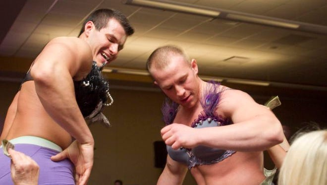Nick Wilson (left) and Alfonse Kolas get donations from women surrounding the catwalk at the annual Bras 4 a Cause event.