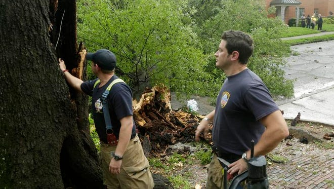 Little Rock firefighters Brandon Gattis (left) and Brad Sanders examine a large oak tree after it fell during a thunderstorm in Little Rock on Friday.