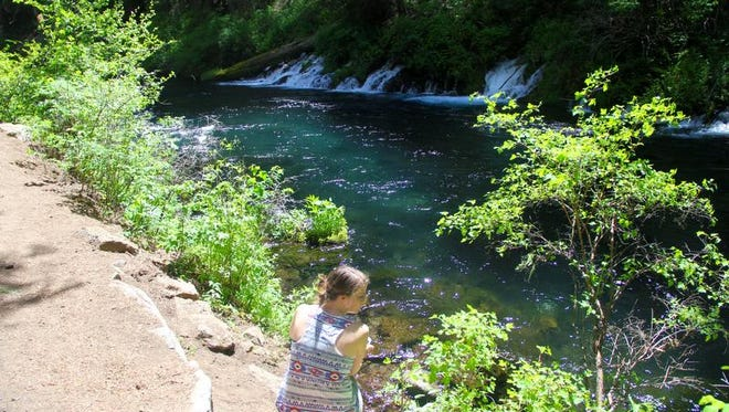 Robyn Orr of Salem sits in front of the springs along the Metolius River Trail.