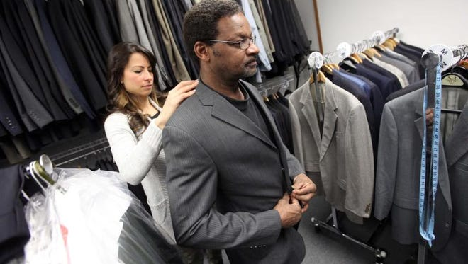 Star Lotta, founder of Suiting Warriors, helps fit Army veteran Joseph Taylor, 58, with a new suit Wednesday.