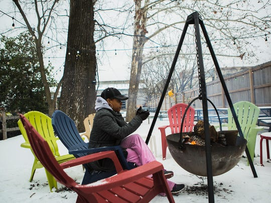 """January 12, 2018 - Shonda Thomas, 46, warms up by a fire pit at Loflin Yard during a rare snow day on Friday afternoon in Memphis, TN. Residents woke to sleet and a smattering of snow as a wintry mix moved in the Memphis metro area. """"Ooooo, I love this,"""" Thomas said. """"This is great. I'm not cold."""""""