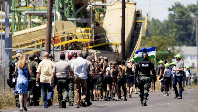 Eugene Police approach protesters in front of Seneca Jones biomass cogeneration plant off Highway 99 north of Eugene, Ore. Monday, July 7, 2014. The sheriff?s office reported that 6 people were inside the mill and two had chained themselves to equipment on. (AP Photo/The Register-Guard, Alisha Jucevic)