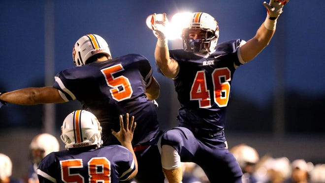 Blackman players Myles Hord (58), left, and Joeseph Sewell (5) and Luke Plunkett (46), right, celebrate Sewell's touchdown against Tucker at Blackman, on Friday Sept. 11, 2015.