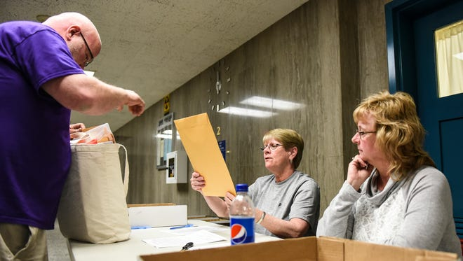 Jeremy Guilliver, a poll worker from the 6th precinct in Lebanon, turns in his ballots to Gladys Walborn and Belinda Spicer as voters headed to the polls to vote in the Pennsylvania primary election on Tuesday, April 26, 2016.