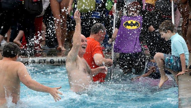 Judge Ben Hall McFarlin Jr. ( center) splashes around during a polar bear plunge in the outdoor pool at SportsCom on Jan. 3, 2014.