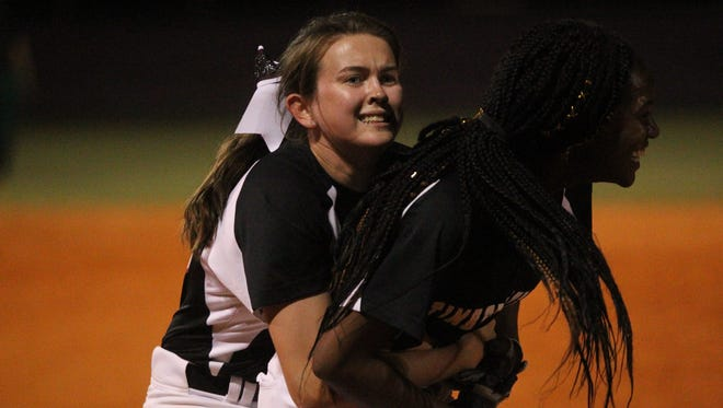 Chiles pitcher Dani Bauer hugs Lamari White and tries to lift her in the air after White hit a walk-off two-run double to help the Timberwolves beat Lincoln 3-2 for a district title.