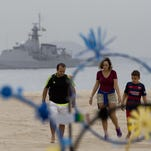 A family walks on the shore of Copacabana beach July 21, back-dropped by a Brazilian navy vessel, in Rio de Janeiro, Brazil. Brazilian police arrested 10 people who allegedly pledged allegiance to the Islamic State group on social media and discussed possible attacks during the Rio de Janeiro Olympics, officials said/