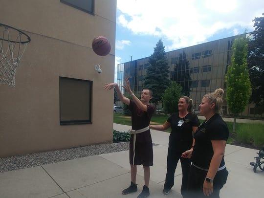 Logan Harter shoots a basketball as part of his rehabilitation