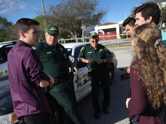 Cameron Kasky Jr., left, and other students of Marjory Stoneman Douglas High School speak with Broward County Sheriff officers.