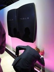 People look at newly-unveiled Tesla Powerwall batteries