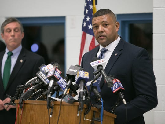 Delaware Department of Correction Commissioner Perry Phelps fields questions from the media as Governor John Carney looks on.