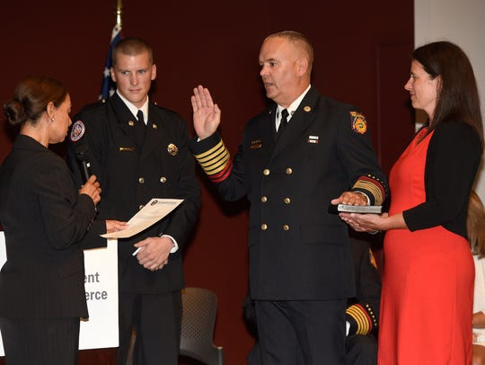Jeff Hussey receives the oath of office Aug. 8 from