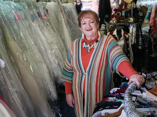 Shireen Jackson, owner, stands among the racks of formal