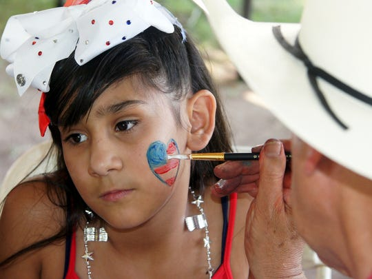 Sophia Zuniga, 9, had her face painted by local artist Paul Hoylen during Tuesday's Fourth of July celebration at Luna County Courthouse Park.