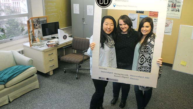 In a Jan. 19, 2015 photo, Oregon State students Whitney Lauren Han, Jodie Davez, and Halie Sutton stand with a decorative Instagram frame they use to promote their publication, Beavers Digest, in their office in Snell Hall at Oregon State University in Corvallis, Ore. (AP Photo/The Corvallis Gazette-Times, Jesse Skoubo)