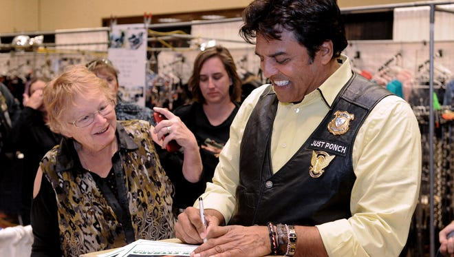 Actor Erik Estrada signs a photo of himself for Norma Soules of Reno at the Street Vibrations event in 2013.