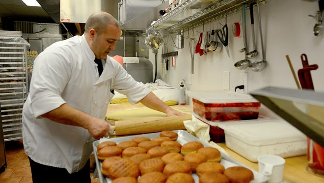 Owner and head chef Pete Counseller rolls out fresh dough as he gets ready to cut some fresh packzi early Tuesday morning at Glazed and Confused bakery in downtown Lansing.