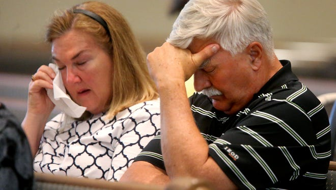 Minerva and Jerry Smith bow their heads to pray at St. Mark's United Methodist Church during a prayer service on behalf of the Huhta family on Tuesday. Church member Jim Huhta is a suspect in the stabbing death of his wife, Mary, who also attended St. Mark's.