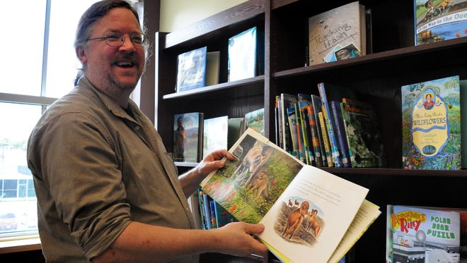 In this Daily Times file photo, Salisbury University's professor of education Ernie Bond shows a book by a winner of the Green Earth Book Award, the first prize in the nation for environmentally friendly children's literature. Bond, who has served on committees that choose the Green Earth Book Award, died suddenly.