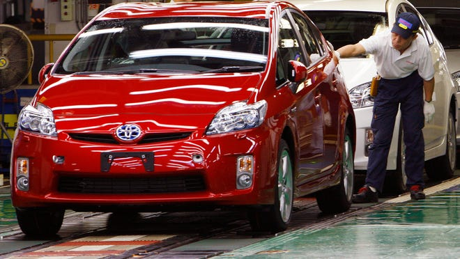In this June 5, 2009 file photo, a Toyota Motor Corp. worker gives the final examination on an newly assembled Prius at Toyota Tsutsumi Plant
