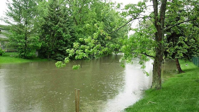 Following a recent downpour, the drainage creek that runs through the Mayfair Village subdivision flooded from a few feet wide to close to 50 feet wide.
