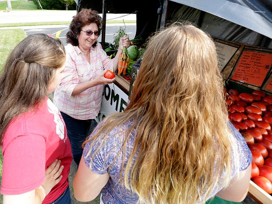 Carol Butzke of Campbellsport (center) buys produce from Brianna Loof and Natalie Hettwer, at their produce stand on Main Street, in Eden on Aug. 27.