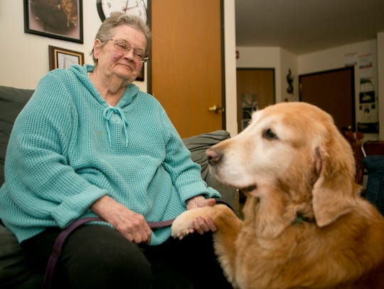 Bonita Swan shakes the paw of her assistance dog, Ann