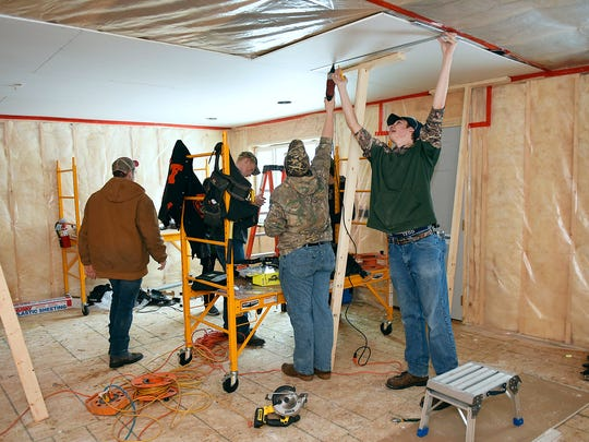 Technical High School students finish drywalling the