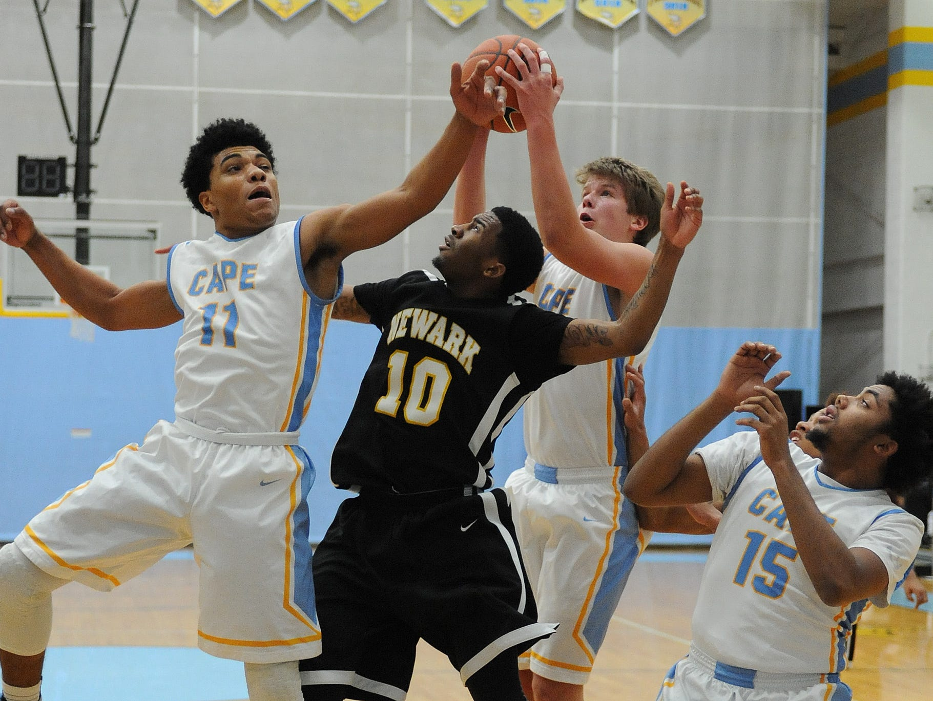 Capes Jerry Harden and Ian Robertson along with Newarks Rahmee Carter fight for the ball as Newark HS (black) and Cape Henlopen HS (white) varsity boys played in the 1st Round of the Boys DIAA Basketball Tournament at Cape Henlopen HS near Lewes on Wednesday March 2nd.