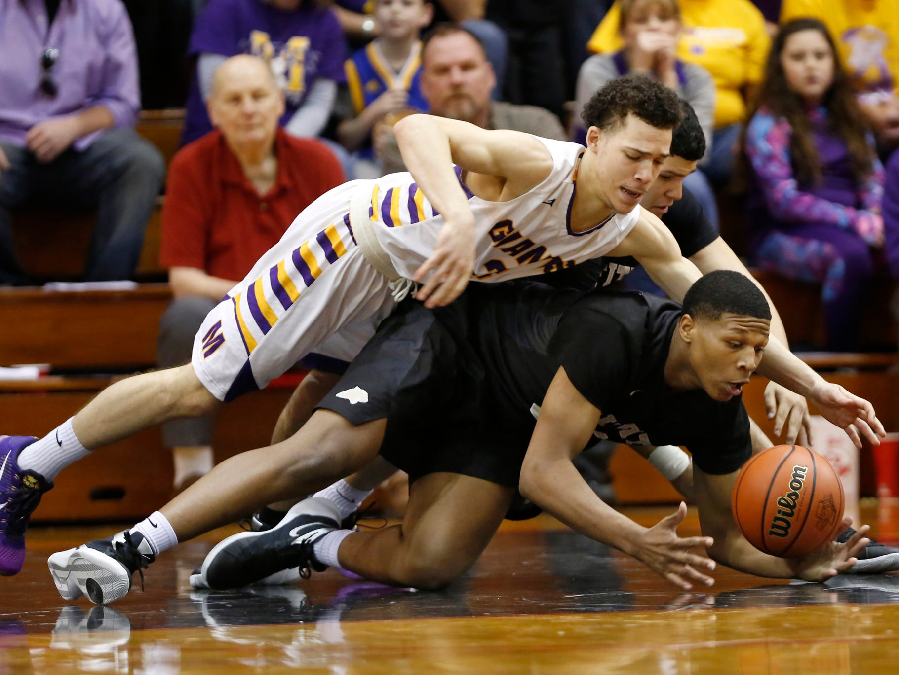 Marion's Tim Leavell, top, and Griffith's Cornell Hampton dive for a loose ball in the Class 3A basketball semistate Wednesday, March 23, 2016, Lafayette Jefferson High School. Marion defeated Griffith 60-58.