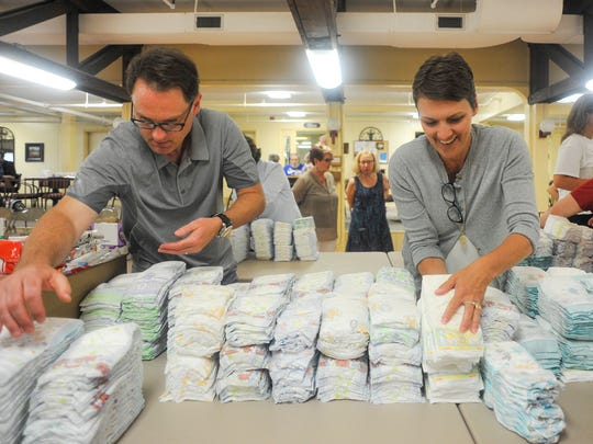 Joel Bark (left) and Kristi Wink grab fresh diapers to pack into small care packages that will be distributed to shelters and other locations to help parents in need of basic necessities such as diapers and formula.